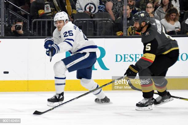 James van Riemsdyk of the Toronto Maple Leafs knocks the puck forward under pressure from Deryk Engelland of the Vegas Golden Knights during the...