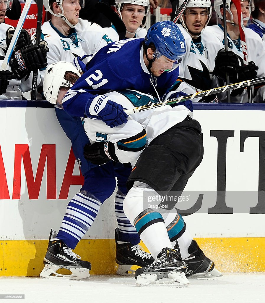 James van Riemsdyk #21 of the Toronto Maple Leafs locks up Mirco Mueller #41 of the San Jose Sharks during game action on March 19, 2015 at Air Canada Centre in Toronto, Ontario, Canada.