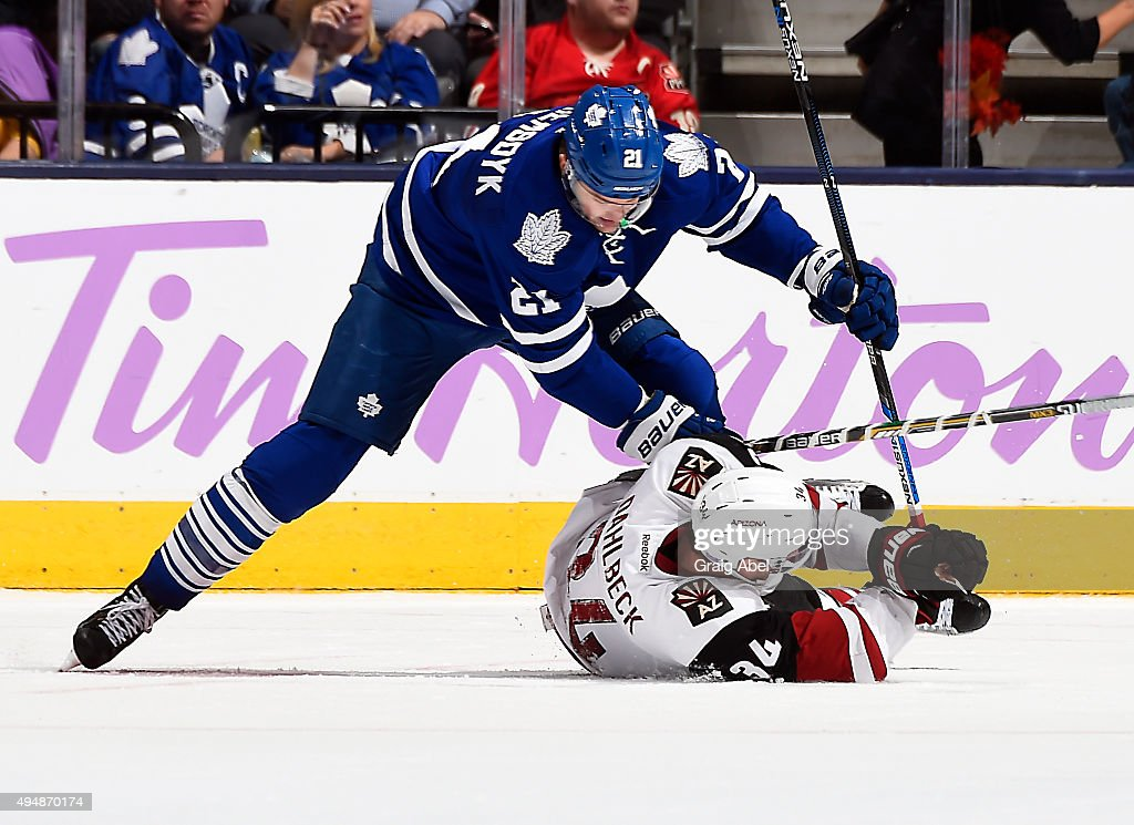 James van Riemsdyk #21 of the Toronto Maple Leafs pins down Klas Dahlbeck #34 of the Arizona Coyotes during game action on October 26, 2015 at Air Canada Centre in Toronto, Ontario, Canada.