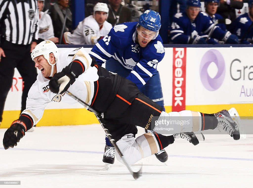 James van Riemsdyk #21 of the Toronto Maple Leafs trips up Ryan Getzlaf #15 of the Anaheim Ducks during NHL action at the Air Canada Centre October 22, 2013 in Toronto, Ontario, Canada.