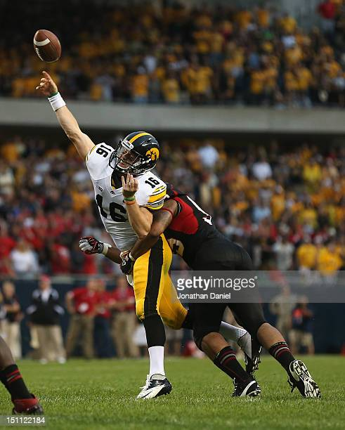 James Vandenberg of the Iowa Hawkeyes is hit while trying to pass for a twopoint conversion by Sean Progar of the Northern Illinois Huskies at...