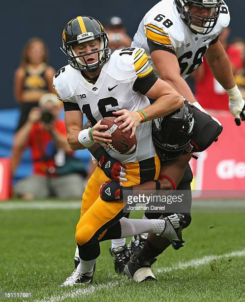 James Vandenberg of the Iowa Hawkeyes is sacked by Alan Baxter of the Northern Illinois Huskies at Soldier Field on September 1 2012 in Chicago...