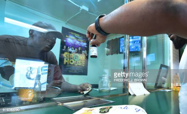 James Varnado working behind the glass at the counter responds to questions about the potency of the cannabis syrup at Virgil Grant's dispensary in...