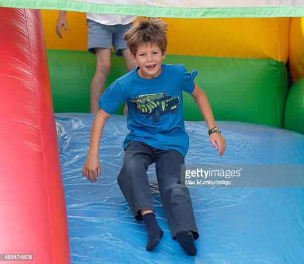 James Viscount Severn plays on an inflatable slide as he attends day 2 of the Festival of British Eventing at Gatcombe Park on August 8 2015 in...