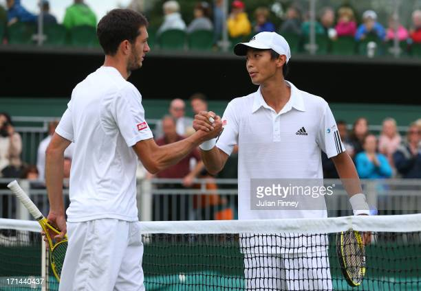 James Ward of Great Britain shakes hands at the net with Lu Yen-Hsun of Taipei after their Gentlemen's Singles first round match on day one of the...