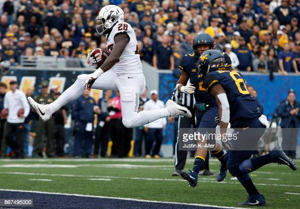 James Washington of the Oklahoma State Cowboys scores on a 13 yard touchdown pass in the first half against the West Virginia Mountaineers at...