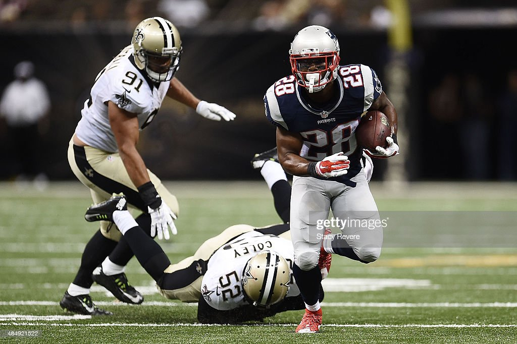 James White #28 of the New England Patriots breaks a tackle by Henry Coley #52 of the New Orleans Saints during the third quarter of a preseason game at the Mercedes-Benz Superdome on August 22, 2015 in New Orleans, Louisiana.