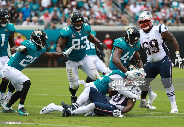 James White of the New England Patriots is brought down by a gang of Jacksonville Jaguars defenders in the first half at TIAA Bank Field on September...