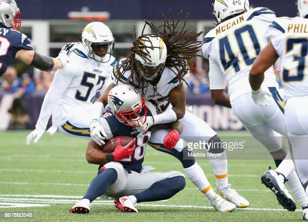 James White of the New England Patriots is tackled by of the Tre Boston of the Los Angeles Chargers during the first quarter of a game at Gillette...