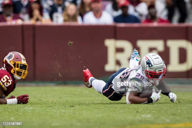 James White of the New England Patriots is tripped up against the Washington Redskins during the first half at FedExField on October 6 2019 in...
