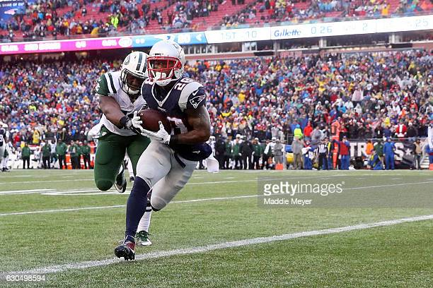 James White of the New England Patriots scores a touchdown ahead of David Harris of the New York Jets during the first half at Gillette Stadium on...