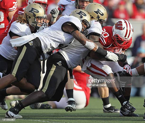 James White of the Wisconsin Badgers is stopped by Albert Evans and Dwayne Beckford of the Purdue Boilermakers at Camp Randall Stadium on November 5,...