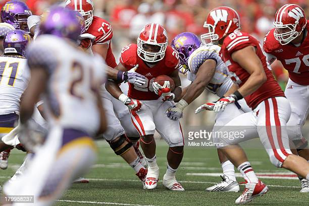 James White of the Wisconsin Badgers runs throw a hole in the defensive line of the Tennessee Tech Golden Eagles during the game at Camp Randall...