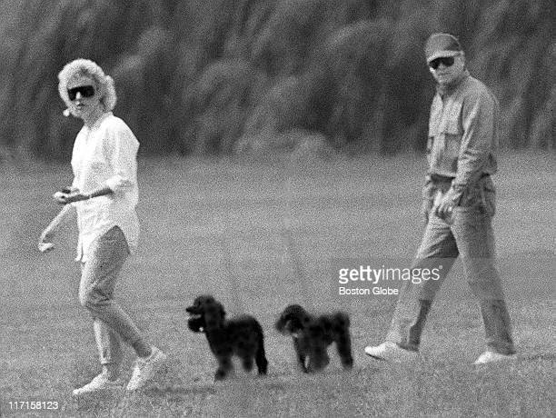 "James ""Whitey"" Bulger and Catherine Greig walk together with Greig's poodles underfoot."
