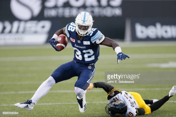 James Wilder Jr #32 of the Toronto Argonauts avoids a tackle by Justin Rogers of the Hamilton TigerCats during a CFL preseason game at Tim Hortons...
