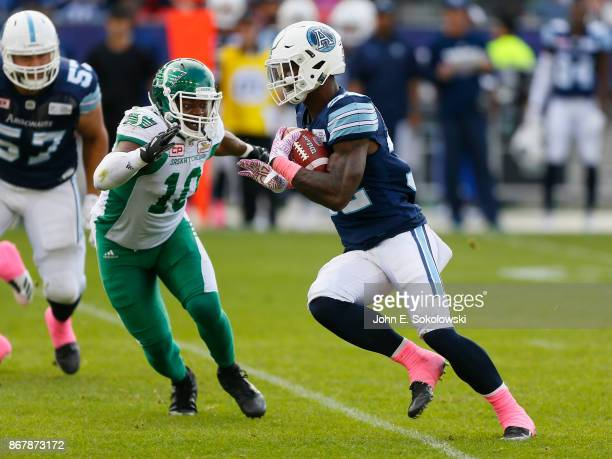 James Wilder Jr #32 of the Toronto Argonauts tries to avoid a tackle by Henoc Muamba of the Saskatchewan Roughriders during a game at BMO field on...
