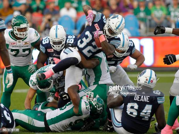 James Wilder Jr #32 of the Toronto Argonauts tries to break a tackle by Ese Mrabure of the Saskatchewan Roughriders during a game at BMO field on...