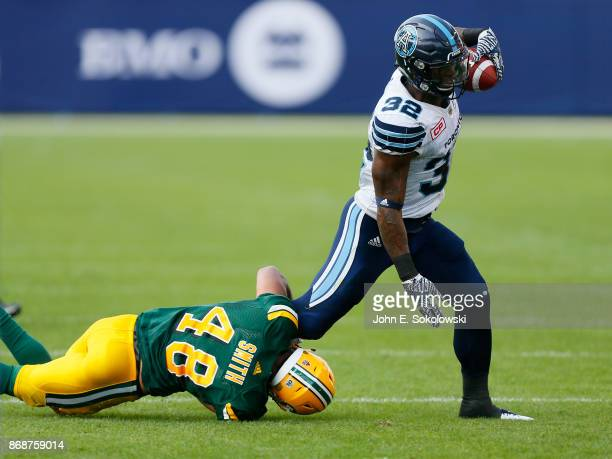 James Wilder Jr #32 of the Toronto Argonauts tries to break a tackle by Blair Smith of the Edmonton Eskimos during a game at BMO field on September...