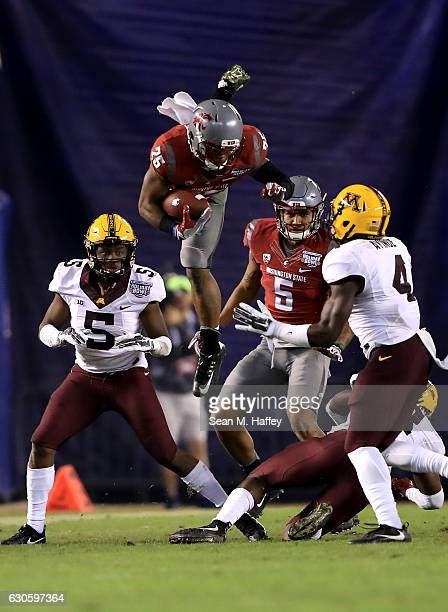 James Williams of the Washington State Cougars leaps over Jalen Myrick and Adekunle Ayinde of the Minnesota Golden Gophers during the second half of...