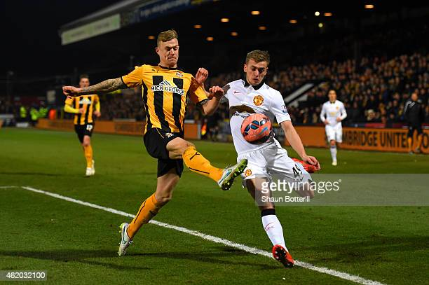 James Wilson of Manchester United battles for the ball with Richard Tait of Cambridge United during the FA Cup Fourth Round match between Cambridge...