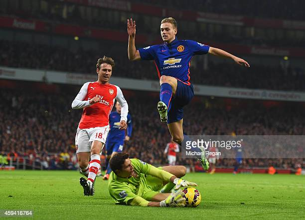James Wilson of Manchester United evades goalkeeper Damian Martinez of Arsenal during the Barclays Premier League match between Arsenal and...