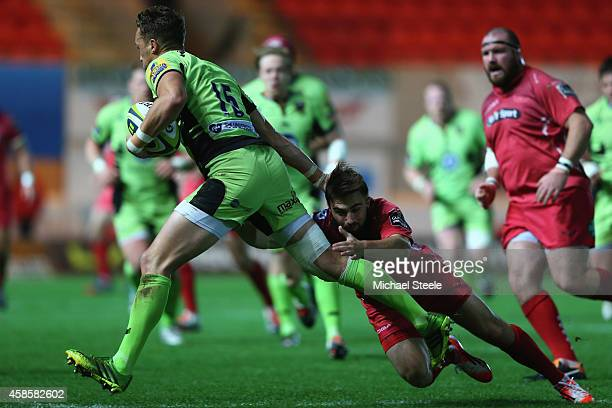 James Wilson of Northampton Saints is tackled by Jordan Williams of Scarlets during the LV=Cup match between Scarlets and Northampton Saints at Parc...