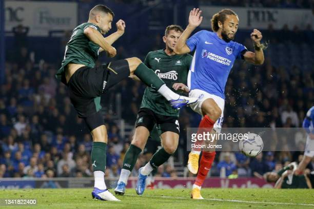 James Wilson of Plymouth Argyle clears from Marcus Harness of Portsmouth FC during the Sky Bet League One match between Portsmouth and Plymouth...