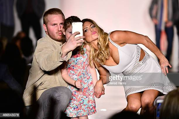 James Wisnewski and wife Nicole pose for a selfie on stage with Jane Jennison at the Anaheim Lady Ducks Fashion Show Luncheon with Bloomingdale's...