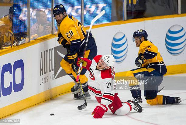James Wisniewski of the Carolina Hurricanes hits the ice as Paul Gaustad and Viktor Arvidsson of the Nashville Predators go after the puck during a...