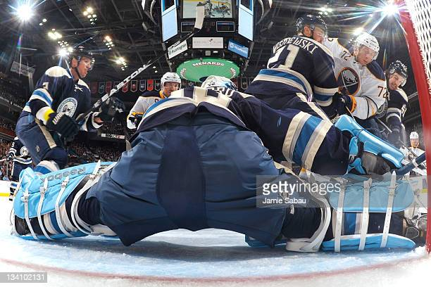 James Wisniewski of the Columbus Blue Jackets and Antoine Vermette of the Columbus Blue Jackets team up to defend Luke Adam of the Buffalo Sabres as...