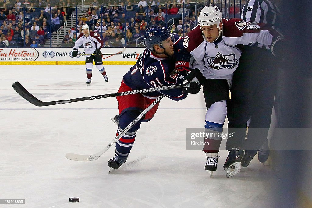James Wisniewski #21 of the Columbus Blue Jackets checks Ryan O'Reilly #90 of the Colorado Avalanche while chasing after the puck during the third period on April 1, 2014 at Nationwide Arena in Columbus, Ohio. Colorado defeated Columbus 3-2 in overtime.