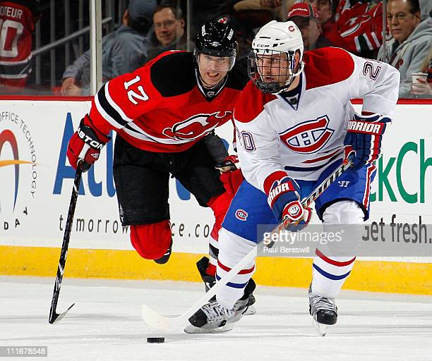 James Wisniewski of the Montreal Canadians skates in front of Brian Rolston of the New Jersey Devils during the first period of an NHL hockey game at...