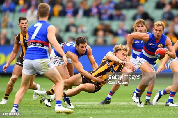James Worpel of the Hawks handballs whilst being tackled by Josh Dunkley of the Bulldogs during the round two AFL match between the Hawthorn hawks...