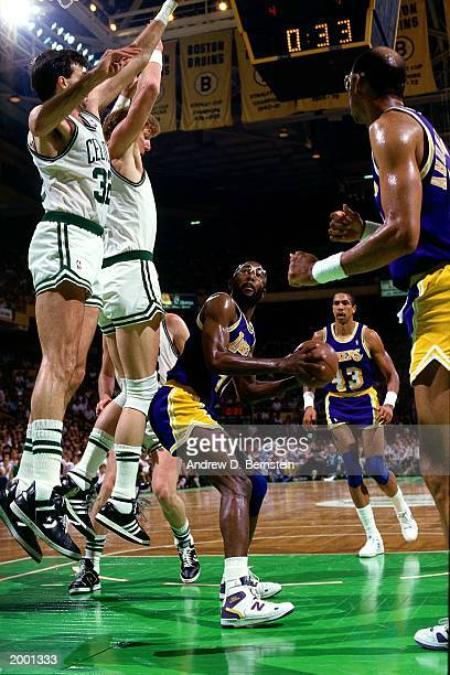 James Worthy of the Los Angeles Lakers fakes against Larry Bird and Kevin McHale of the Boston Celtics during the 1991 season NBA game at the Boston...