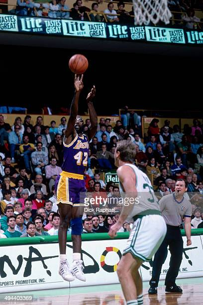 James Worthy of the Los Angeles Lakers takes a shot against Larry Bird of the Boston Celtics during a game played in 1992 at the Boston Garden in...