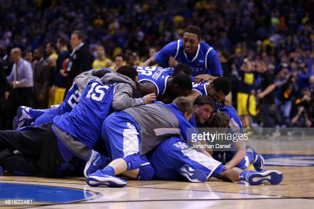 James Young of the Kentucky Wildcats celebrates with his teammates on the court after defeating the Michigan Wolverines 75 to 72 in the midwest...