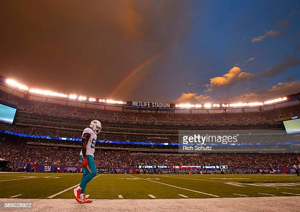 James-Michael Johnson of the Miami Dolphins walks down the sideline as a rainbow appears over head before an NFL preseason game against the New York...