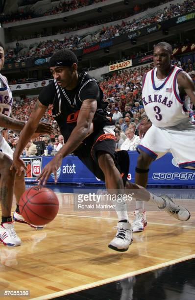 JamesOn Curry of the Oklahoma State Cowboys dribble drives baseline past Russell Robinson of the Kansas Jayhawks during the quarterfinals round of...