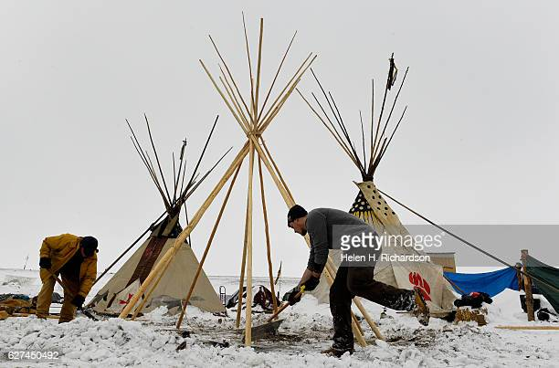 Jameson Dargen, right, helps Peter Anderson, left, shovel out snow to build their teepee at Oceti Sakowin Camp on the edge of the Standing Rock Sioux...
