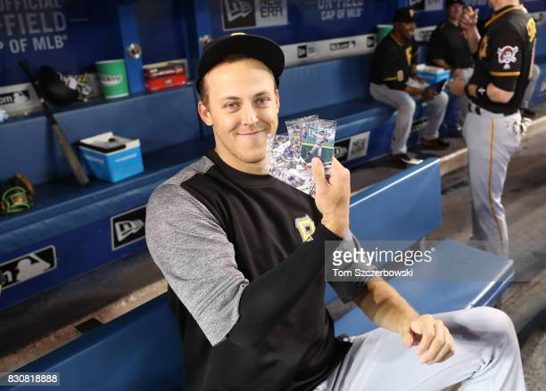 Jameson Taillon of the Pittsburgh Pirates holds up selected Topps baseball cards on National Baseball Card Day before the start of MLB game action...