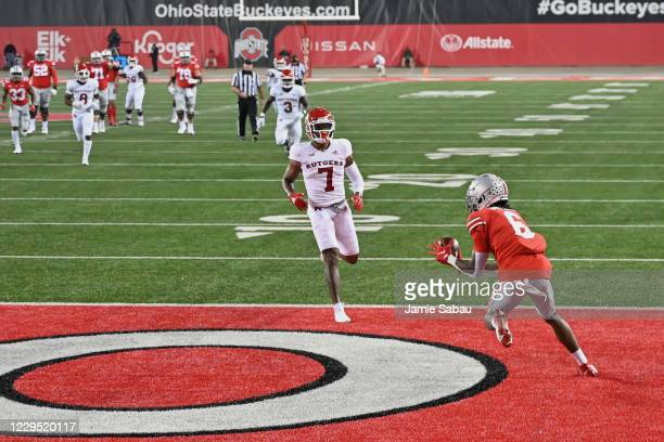 Jameson Williams of the Ohio State Buckeyes catches a 38-yard touchdown pass in the first quarter as Brendon White of the Rutgers Scarlet Knights...