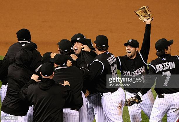 Jamey Carroll and the Colorado Rockies celebrate defeating the Arizona Diamondbacks in Game Four of the National League Championship Series at Coors...