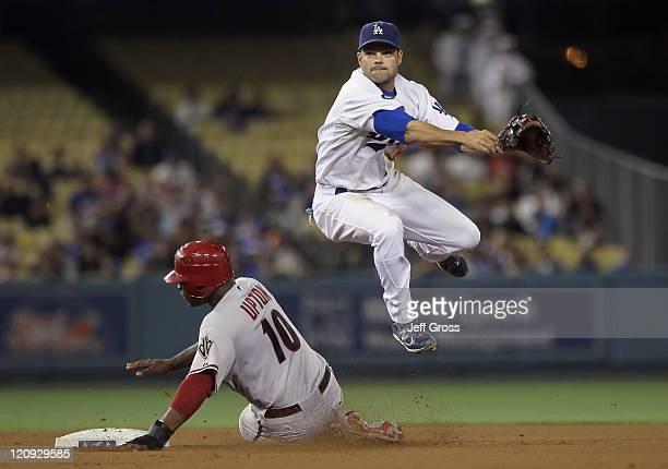 Jamey Carroll of the Los Angeles Dodgers leaps over Justin Upton of the Arizona Diamondbacks at Dodger Stadium on July 30 2011 in Los Angeles...