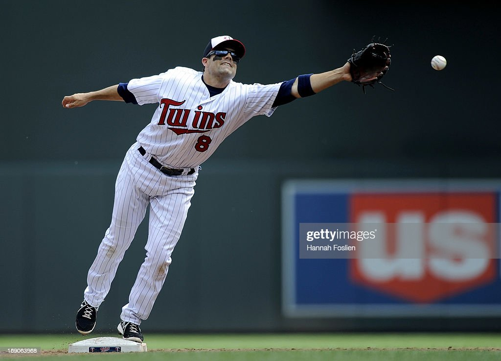 Jamey Carroll #8 of the Minnesota Twins reaches for the baseball thrown by teammate Trevor Plouffe #24 during the third inning of the game against the Boston Red Sox on May 19, 2013 at Target Field in Minneapolis, Minnesota.
