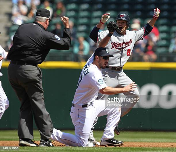 Jamey Carroll of the Minnesota Twins reacts after being tagged out on a steal attempt at second base by Dustin Ackley of the Seattle Mariners at...