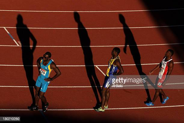 Jamial St John Rolle of the Bahamas Ramon Gittens of Barbados and David Lescay of Cuba stand on the track after competing in the men's 100m semifinal...