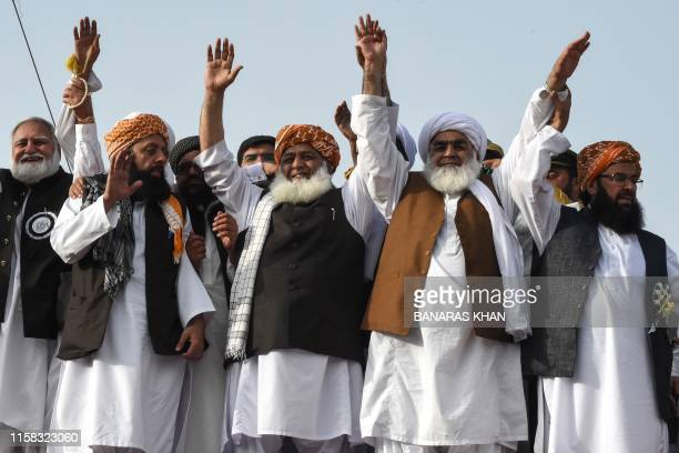 Jamiat UlmaeIslam political party leader Maulana FazalurRehman flanked by party leaders waves to supporters during antigovernment rally in Quetta on...