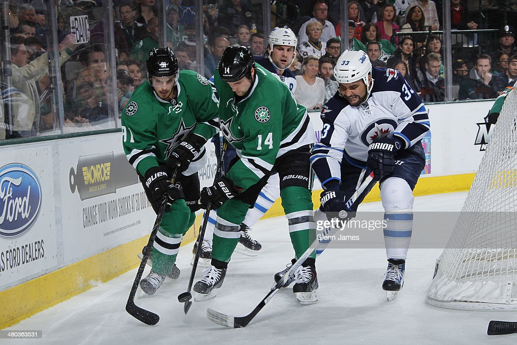 Jamie Benn #14 and Tyler Seguin #91 of the Dallas Stars try to keep the puck away against Dustin Byfuglien #33 of the Winnipeg Jets at the American Airlines Center on March 24, 2014 in Dallas, Texas.