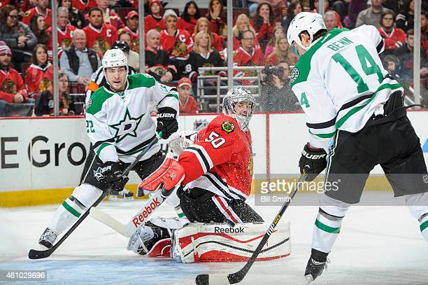 Jamie Benn of the Dallas Stars hits the puck to score on goalie Corey Crawford of the Chicago Blackhawks as Colton Sceviour watches from behind...