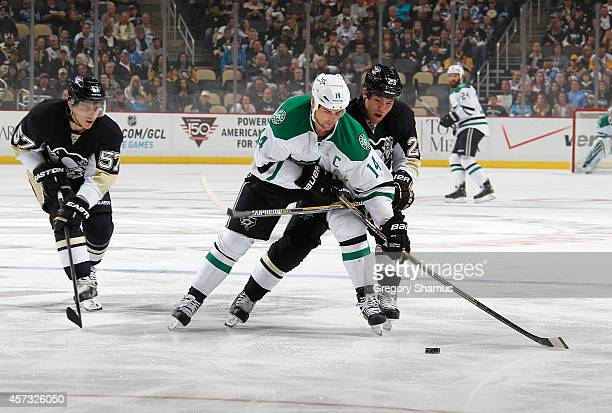 Jamie Benn of the Dallas Stars moves the puck up ice in front of Marcel Goc and Steve Downie of the Pittsburgh Penguins at Consol Energy Center on...